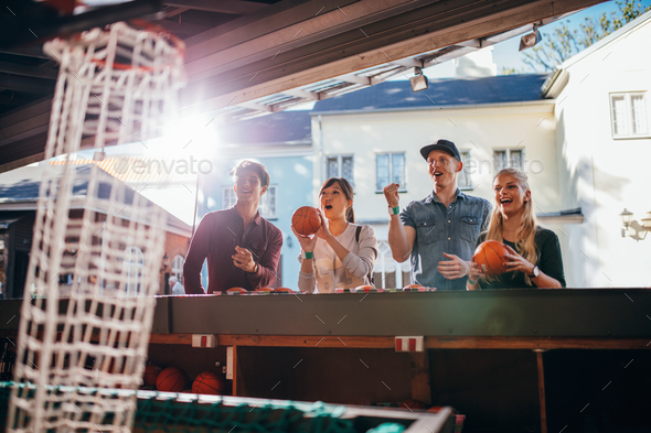 Young people shooting hoops at amusement park - Stock Photo - Images