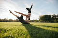 Healthy young couple doing acro yoga on grass