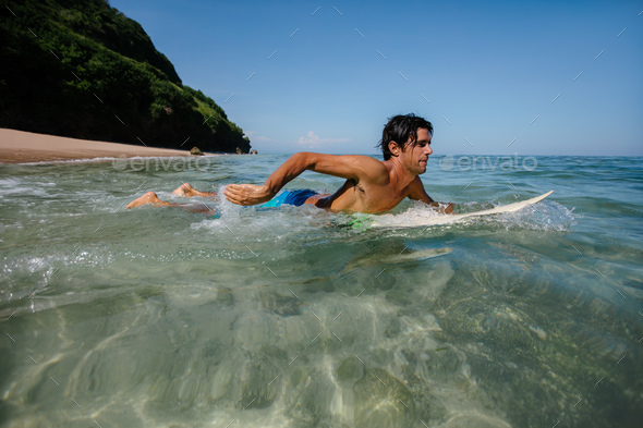 Young man water surfing in ocean - Stock Photo - Images