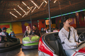 Friends having fun on bumper cars in amusement park - PhotoDune Item for Sale