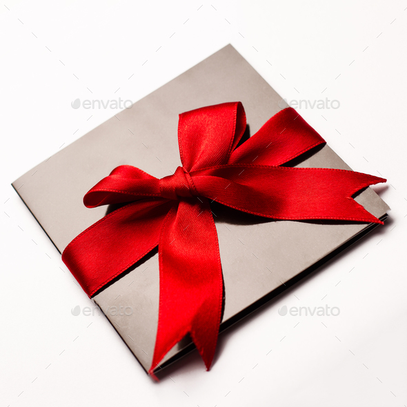 Black paper card with red textile ribbon isolated on white - Stock Photo - Images