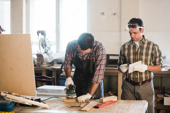 two man polishes boards. carpenter with a sander - Stock Photo - Images