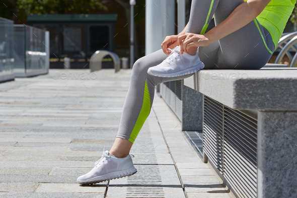 Woman tying shoelaces before running outdoor in the city - Stock Photo - Images