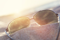 Sunglasses on sand at sunset, beach and ocean in the background. - PhotoDune Item for Sale