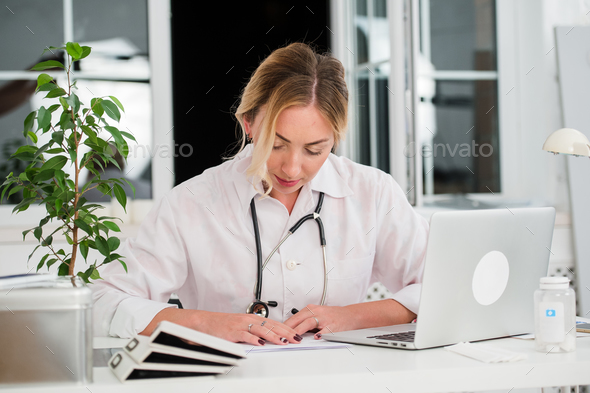 Mid adult female doctor reading documents at office desk - Stock Photo - Images