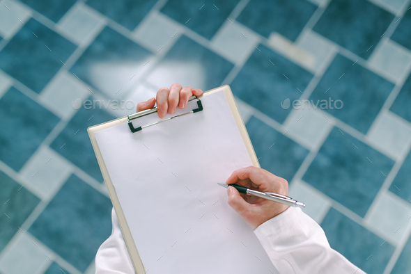 Female doctor in white uniform writing on clipboard paper - Stock Photo - Images