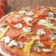 Cooking Pizza. A Young Woman Putting Pieces Of Ingredients On The Pizza Base Greased With Tomato - VideoHive Item for Sale