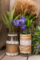 Rustic still life: dried flowers bunch and vases on vintage wooden background.
