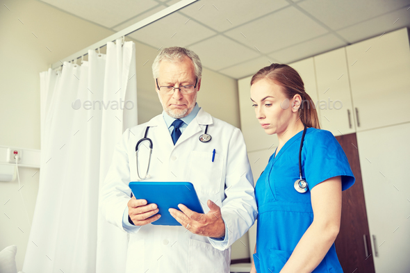 senior doctor and nurse with tablet pc at hospital - Stock Photo - Images