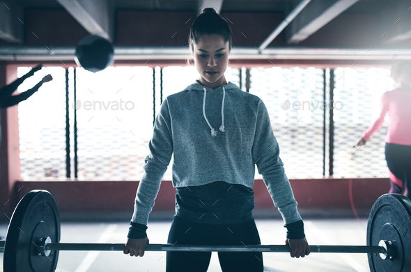 Fit healthy woman lifting a weight barbell - Stock Photo - Images