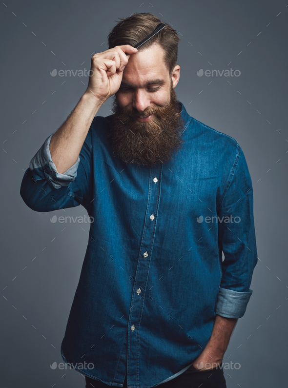 Cheerful man in beard combing his hair - Stock Photo - Images