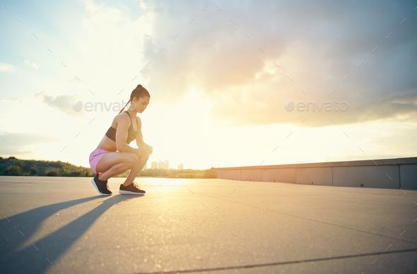 Female athlete squatting near ground outside - Stock Photo - Images