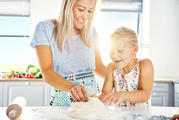 Excited little girl helping her mother make pastry - Stock Photo - Images