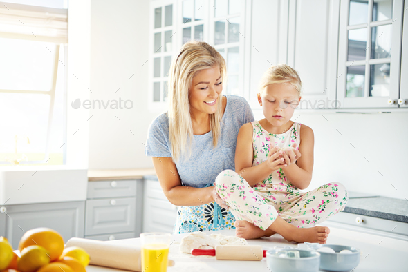 Happy woman helping little girl prepare food - Stock Photo - Images