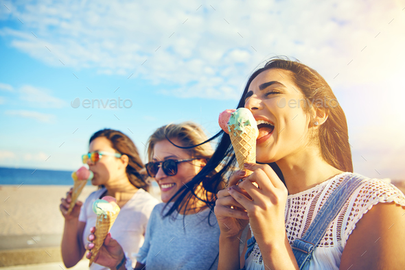 Three young woman eating ice cream at the seaside - Stock Photo - Images