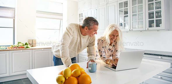 Senior couple relaxing in a kitchen with a laptop - Stock Photo - Images
