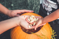 close up of woman's and child hands pulls seeds fibrous material from pumpkin