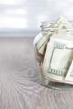 Money. Dollars in open jar on grey wooden background.  Copy space.