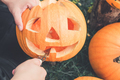 close up of man's hand who cuts with knife pumpkin as he prepares jack-o-lantern. Halloween.