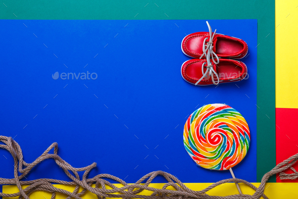 Small red boat shoes near big multi-colored lollipop - Stock Photo - Images