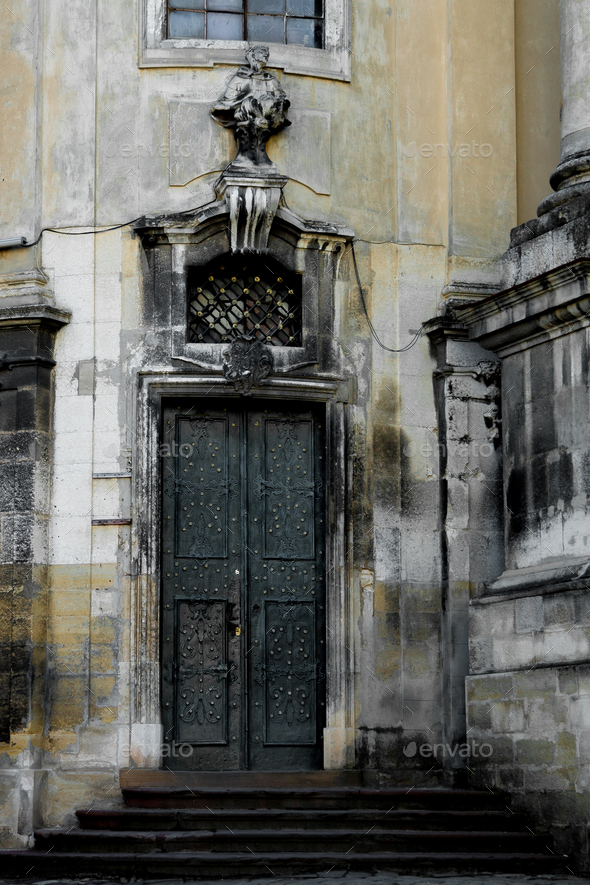 Facade of the Dominican Cathedral, Lviv, Ukraine. Fragment   with door and window  metal grill. - Stock Photo - Images