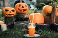 Halloween cocktail with pumpkins decoration on background. Punch for a party. Jack-o-Lantern
