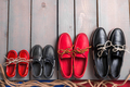 Family boat shoes on wooden background.