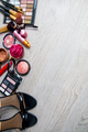 Set of decorative cosmetics and brushes near black heeled sandals on grey wooden background.