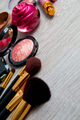 Set of decorative cosmetics and brushes on grey wooden background. Various makeup products. Top