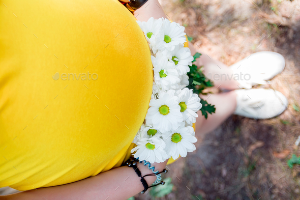 Close up on tummy of pregnant woman, wearing yellow dress, holding in hands bouquet chamomile - Stock Photo - Images