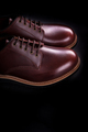 Brown oxford shoes on black background. Back view. Copy space.