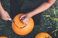 close up of man's hand cuts lid from pumpkin as he prepares jack-o-lantern. Halloween.