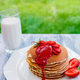 Pancakes with fresh strawberry and mint on white plate on pink wooden background in garden - PhotoDune Item for Sale