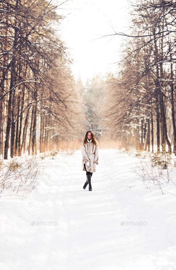 Girl walking in snow. Winter, cold and people concept - Stock Photo - Images