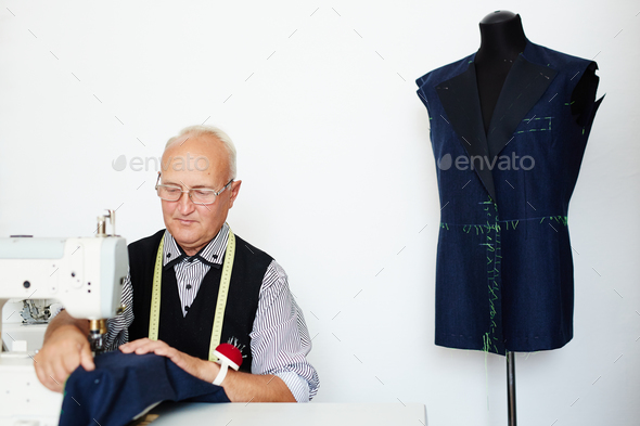 Tailor working at sewing machine - Stock Photo - Images