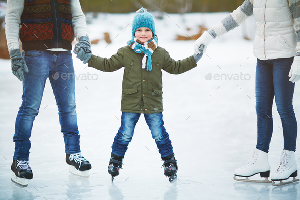 Smiling boy skating with parents - Stock Photo - Images