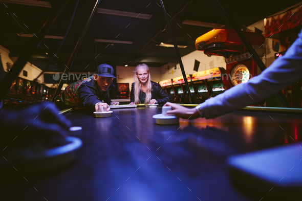 Young man and woman playing air hockey game - Stock Photo - Images