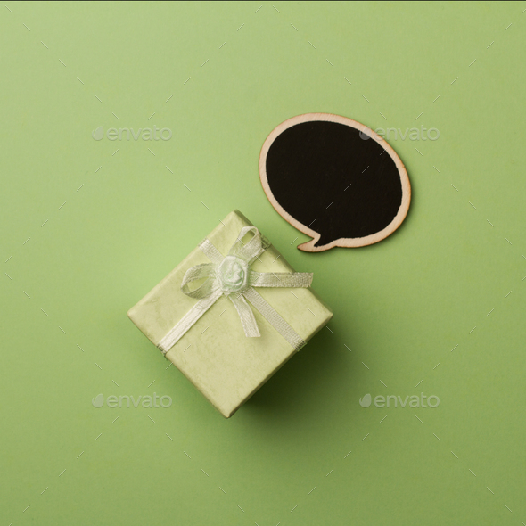 Concept little gift box with wooden speech bubble for messages - Stock Photo - Images
