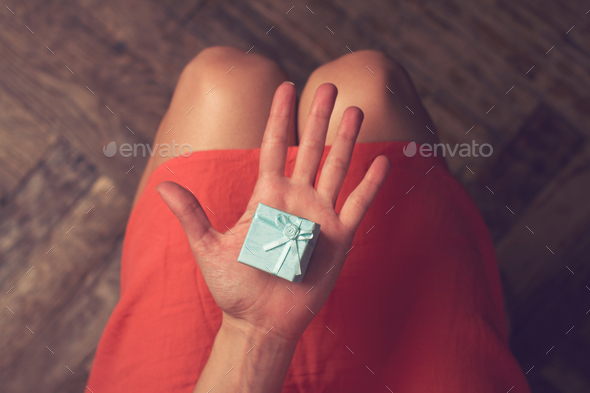 Woman holding a cardboard small gift blue box with ribbon - Stock Photo - Images