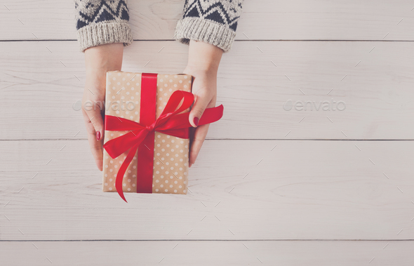 Woman's hands give christmas gift in present box - Stock Photo - Images
