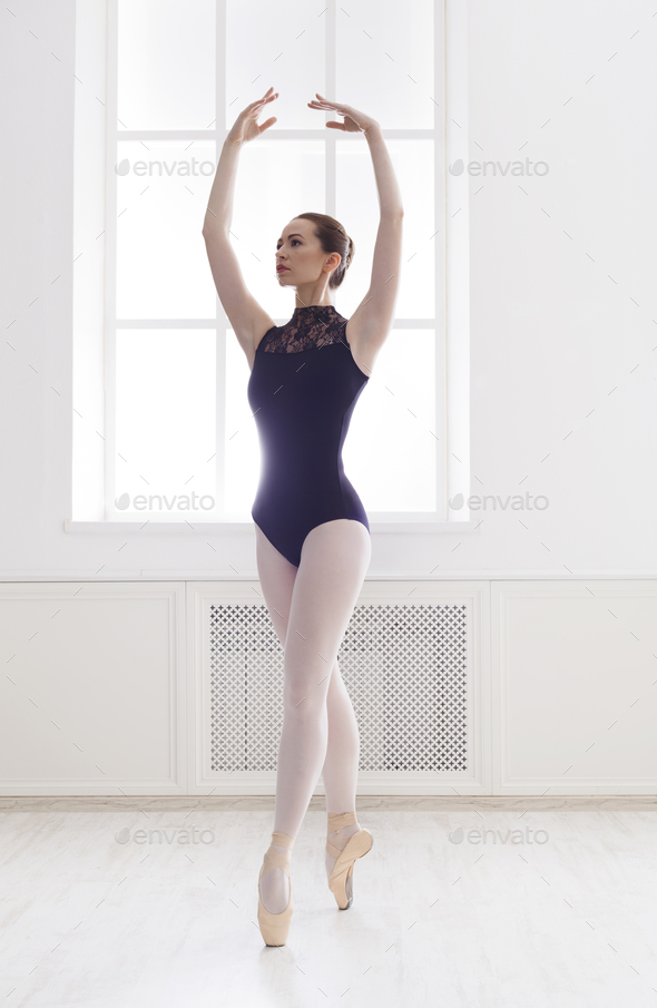 Beautiful ballerine stands in fifth ballet position
