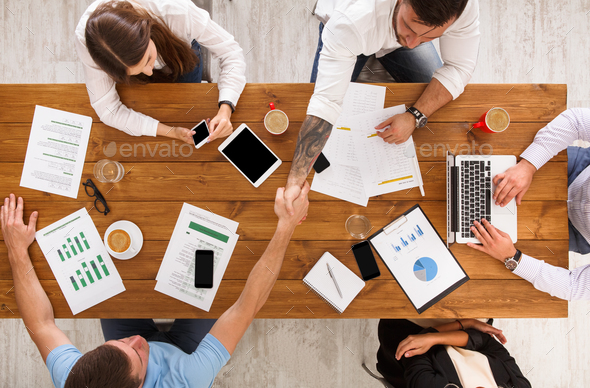 Business people group handshake in office, top view - Stock Photo - Images