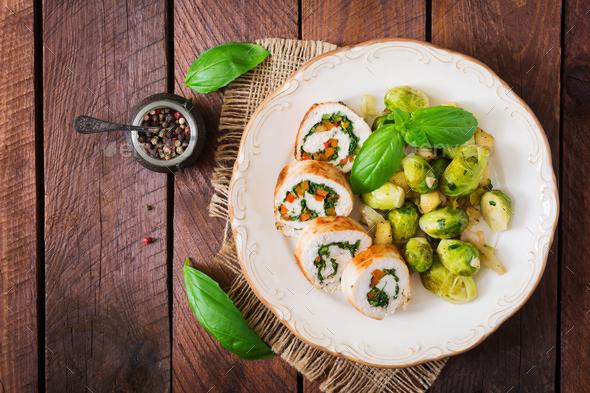 Chicken rolls with greens, garnished with stewed Brussels sprouts, apples and leeks  - Stock Photo - Images