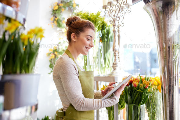 woman with tablet pc computer at flower shop - Stock Photo - Images