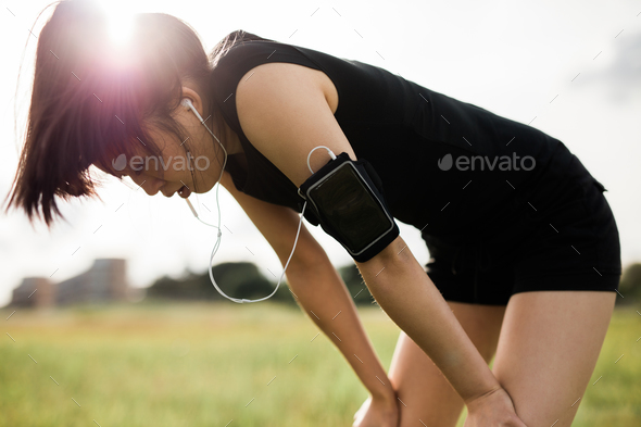 Sportswoman taking break from running workout. - Stock Photo - Images