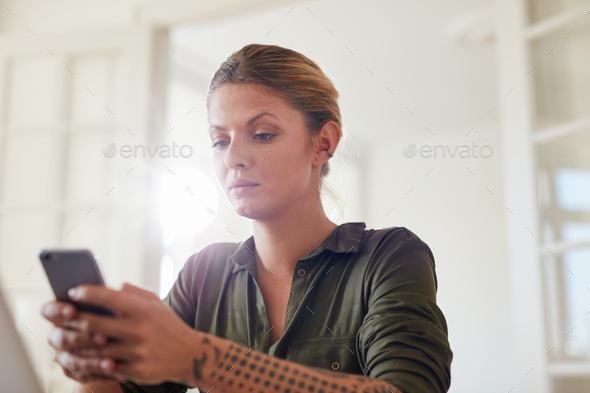 Beautiful young woman using mobile phone at home - Stock Photo - Images