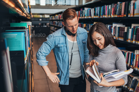 Students choosing a book in a library - Stock Photo - Images