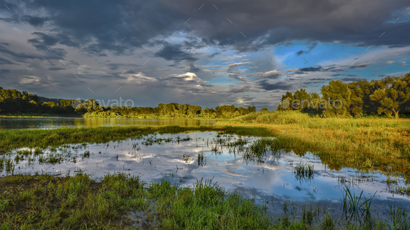 Cloudy sky over beautiful flood plain landscape - Stock Photo - Images