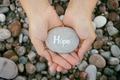 Woman holding stone with the word Hope in her palms - PhotoDune Item for Sale