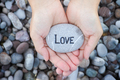 Woman holding stone with the word Love in her palms - PhotoDune Item for Sale